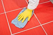stock photo of mortar-joint  - Worker With Yellow Gloves And Blue Towel Clean Red Tiles Grout - JPG