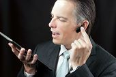 Businessman Using Tablet Adjusting Headset Earpiece.