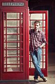 Young Man Standing At Telephone Box