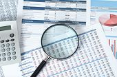 calculator and magnifying glass over financial reports