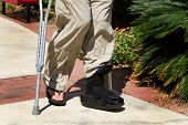 picture of crippled  - Man uses crutches along with a foot and ankle brace to help him walk after an accidental injury - JPG