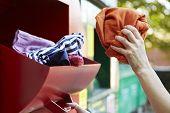 Woman Recycling Clothes At Clothing Bank