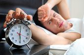 stock photo of early-man  - Man sleeping with alarm clock in foreground - JPG