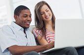 Kreative Designer, die zusammen auf einem Laptop arbeiten, während sie auf einem Sofa saß, sind