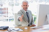 Smiling businessman reaching out arm for handshake at his desk