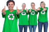 Happy women wearing green recycling tshirts giving thumbs up on white background