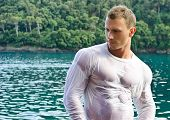 image of wet t-shirt  - Attractive young bodybuilder by the sea with wet shirt on serious expression - JPG