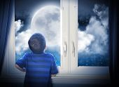 stock photo of moon stars  - A young boy is looking out of the window at a big moon in the dark night with stars and space for an astronomy or imagaination concept - JPG
