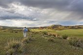 male hiker with a backpack contemplates sunset over Red Mountain Open Space near Fort Collins, spring scenery