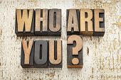 who are you question in vintage letterpress wood type on a grunge painted barn wood background