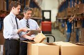 foto of warehouse  - Businessmen Checking Boxes With Digital Tablet And Scanner - JPG