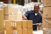 image of dispatch  - Worker In Warehouse Preparing Goods For Dispatch - JPG