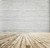 Background of aged grungy textured white brick and stone wall with light wooden floor with whiteboar
