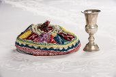 Kiddush Cup And Colorful Yalmulke On Linen Tablecloth