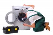 stock photo of jumpsuits  - A repairman holding a spanner and posing next to a washing machine isolated on white background - JPG