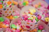 stock photo of sweetie  - Small Cups of coloured popcorn at a party - JPG