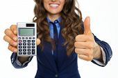 Closeup On Smiling Business Woman Showing Calculator And Thumbs Up