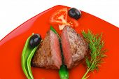 meat savory : grilled beef fillet mignon on red plate with tomatoes apples and pepper isolated over