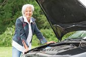 Senior woman standing behind a broken car