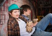 stock photo of underage  - Two drunk young European men sitting outside - JPG