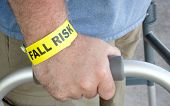 picture of wrist  - A man wearing a fall risk bracelet around his wrist using a walker