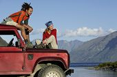 Mann und Frau, sitting on Top of Jeep nahe Bergsee