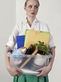 Female office worker carrying personal belongings indoors