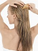 Rear view of a young blond woman combing her wet hair against white background
