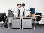 Side view of a business couple kissing over desks in the office