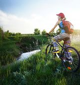 Young lady standing with bicycle on a wild meadow by a river at sunset