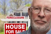 Depressed Senior Man in Front of Foreclosure Real Estate Sign and House.