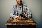 Hipster With Vintage Camera At Old Desk