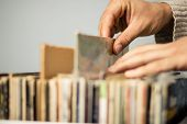 image of thrift store  - Close Up On Hands Browsing Record Store - JPG