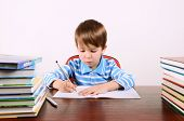 stock photo of diligent  - little boy sits at his desk and carefully writing in exercise book - JPG