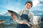 stock photo of saltwater fish  - Fisherman holding a big atlantic salmon fish in the fishing harbor - JPG
