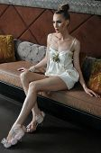 Model wearing designers dress and shoes posing on the sofa