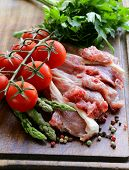 raw meat, lamb chops with vegetables on wooden board