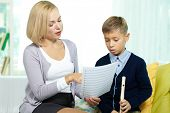 Portrait of pretty tutor showing notes to diligent pupil with the flute