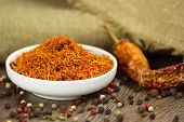 Saffron in saucer with natural pepper and chili on wooden background