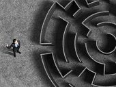 Top view of successful businessman standing near the entrance of labyrinth
