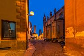 Narrow cobbled street among houses, church and medieval towers early in the morning in Alba, Italy.