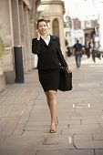 Businesswoman on phone walking down street