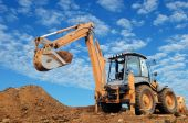 stock photo of power-shovel  - Excavator Loader with rised backhoe standing in sandpit with over cloudscape sky - JPG