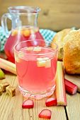 Compote From Rhubarb In Glass And Jug With Bread On Board