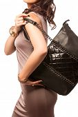 Closeup of woman with quilted fashion leather black bag with chains. Isolated on the white studio ba