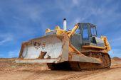 Heavy Bulldozer With Half Raised Blade In Sandpit
