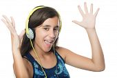 Beautiful hispanic teenager listening to music on her headphones and dancing  isolated on white