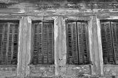 stock photo of abandoned house  - Broken wooden window shutters and textured wall of an abandoned house - JPG