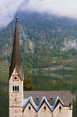 Slender belfry and Lutheran church on the shore of Lake Hallstatt. On the opposite shore of the lake