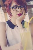 Cute hipster teenage girl daydreaming in a coffee shop